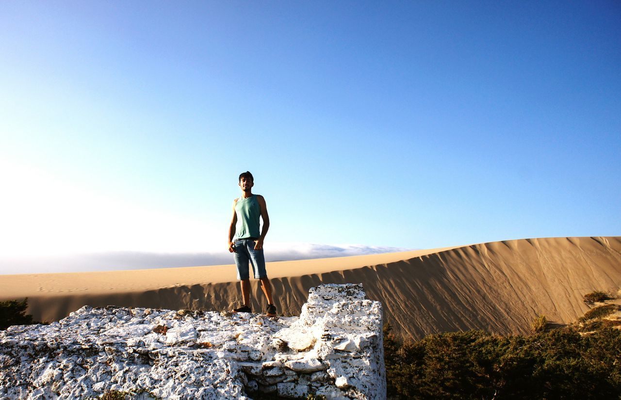 clear sky, full length, one person, real people, lifestyles, nature, copy space, blue, standing, mid adult men, leisure activity, outdoors, rock - object, day, casual clothing, low angle view, sky, scenics, young adult, beauty in nature