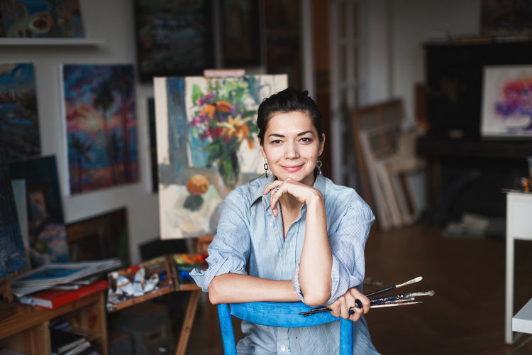 A young smiling brunette woman artist in her Studio is holding a brush. Near her easel, paintings and various art equipment. Artist Studio Art And Craft Beautiful Woman Brush Casual Clothing Creativity Emotion Focus On Foreground Front View Happiness Indoors  Looking At Camera One Person Painter Portrait Real People Smiling Standing Table Young Adult Young Women International Women's Day 2019