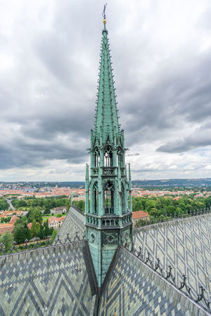 The copper bell tower and roof detail of the St Vitus Cathedral in Prague, with the cityscape in the background on a cloudy day. Architecture Architecture Building Exterior Built Structure Church City Cityscape Cloud - Sky Czech Republic Europe High Angle View Of Prague Historical Building History Nature No People Outdoors Place Of Worship Prague Prague Czech Republic Religion Sky Spirituality St Vitus Cathedral Steeple Travel Destinations