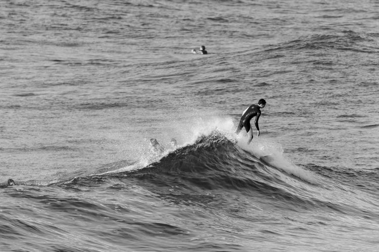 Close-up of man surfing on waves in sea