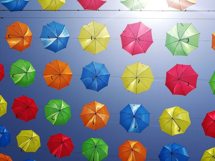 Low angle view of colorful umbrellas against sky