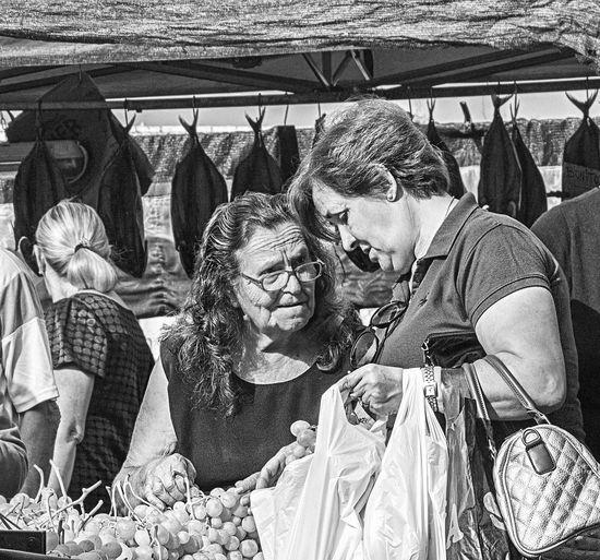 Santa Pola food market. Choosing the weekly shop, grape picking is serious business. Bags Buying Choices Discussion Food Grape Picking Grapes Grocery Market Stall Outdoors People Santa Pola Shopping Women