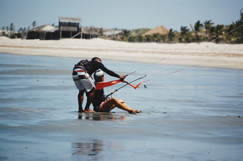 Kite school. woman at first lesson of kitesurf with her teacher in the beach