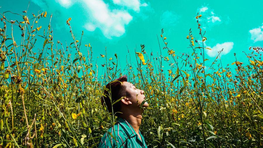 Man amidst blooming flowers against blue sky