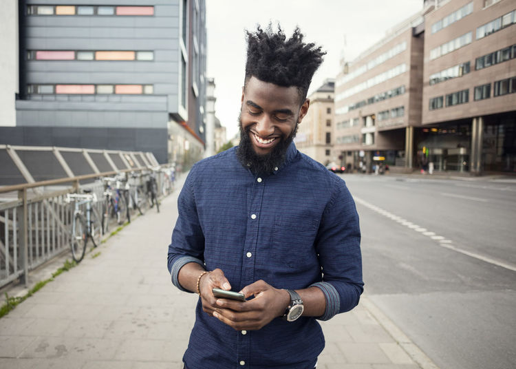 Young man using mobile phone standing in city