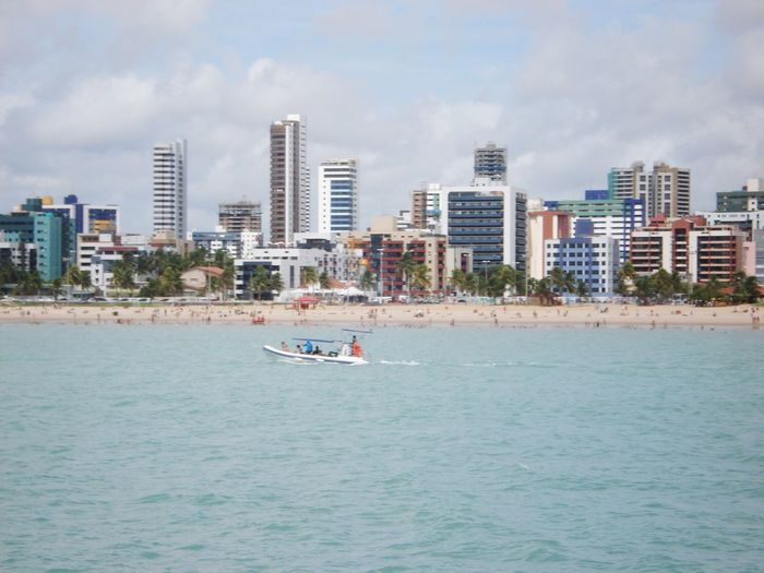 Scenic view of sea against buildings in city