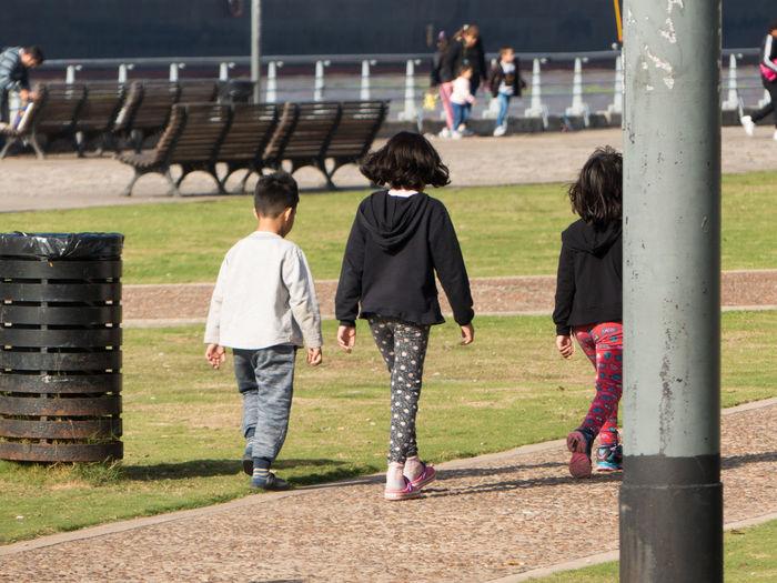 Rear view of children walking on land in park