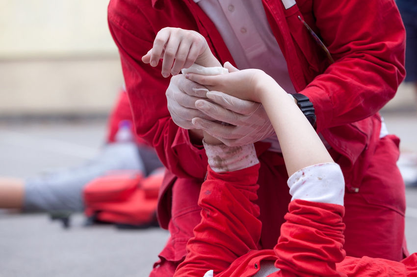 Paramedic giving help to an injured person after accident Injured Doctor  Emergency First Aid Paramedic Accident Ambulance Staff Bandaging Gauze Health Care Help Human Hand Injury Medical Patient Protective Glove Rescue Training Unrecognizable Person Urgency Wound