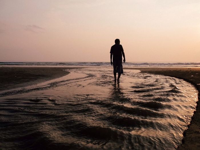 Silhouette of woman standing on beach at sunset