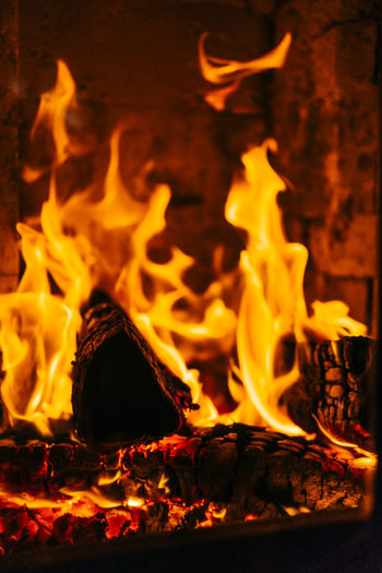 Close-up of fireplace with burning logs of wood. Burning Fire Flame Heat - Temperature Fire - Natural Phenomenon Glowing Log Motion Close-up Wood Orange Color Firewood No People Nature Wood - Material Night Bonfire Long Exposure Fireplace Event Campfire