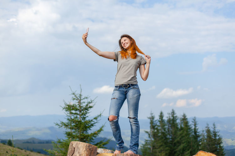 Full length portrait of happy woman standing against sky