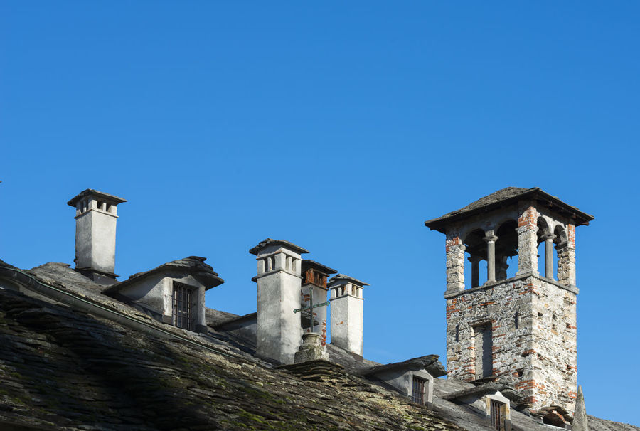 Many chimneys on the roof Abbundance, Antique Architecture Blue Sky Building Exterior Built Structure Chimney Chimney Stacks Clear Sky Color Copy Space Day Front View Full Frame House Many No People Old Outdoors Part Of Roof Rustic Stack Sunny