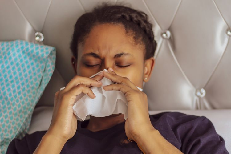 Close-up of woman with cold and flu at home