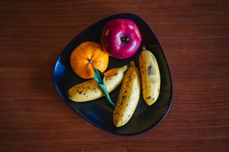 Fruits on a wooden table Healthy Eating Food And Drink Food Fruit Wellbeing Freshness Table Banana Still Life Indoors  High Angle View Wood - Material No People Directly Above Apple - Fruit Close-up SLICE Bowl Group Of Objects Plate Purple Wooden Table
