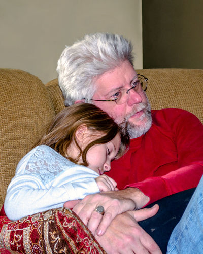 Cute Granddaughter With Grandfather Sleeping On Bed At Home