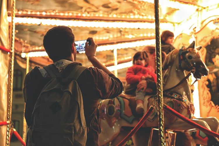 Rear view of photographer photographing at night