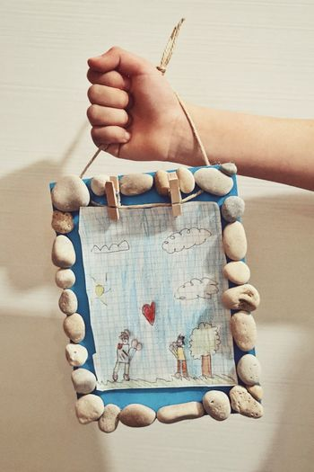 Close-up of hand holding paper hanging on wood