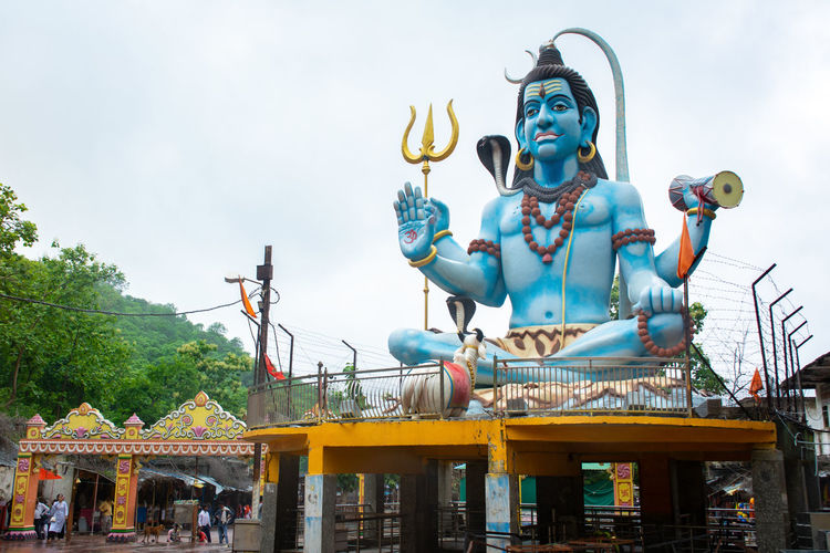 Low angle view of statue in amusement park against sky