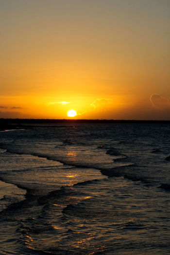 Caribbean sunset with a golden sky and tiny waves coming unto the beach Sunset Sky Water Sea Scenics - Nature Beauty In Nature Sun Orange Color Horizon Over Water Horizon Tranquility Tranquil Scene Nature Idyllic No People Sunlight Beach Waterfront Land Outdoors