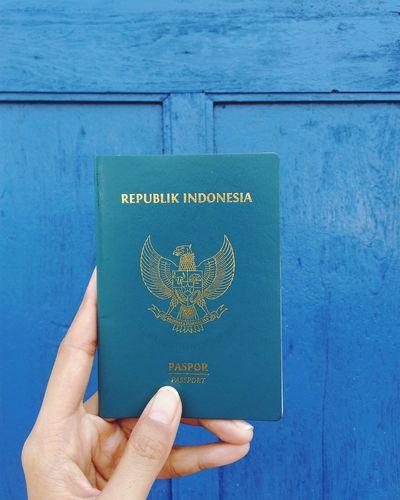 Cropped hand holding passport against blue wooden door