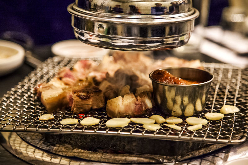 Close-Up Of Pork Meat With Bowl And Garlic On Barbecue Metal Grate