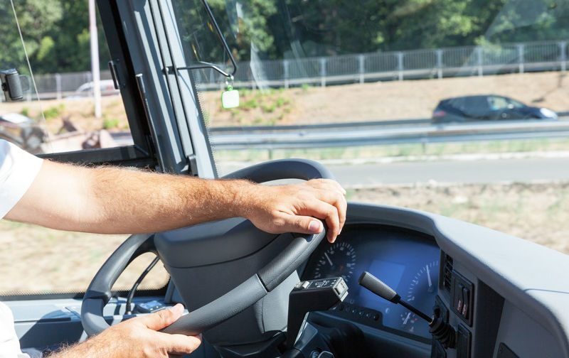 Cropped hands of man driving bus in city