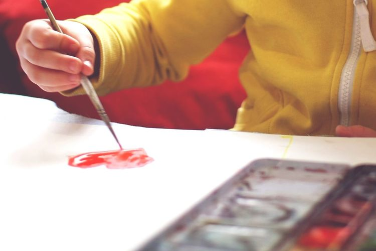 Close-Up Mid Section Of A Kid Painting Heart
