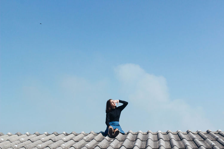 Woman shielding eyes while sitting on rooftop against sky