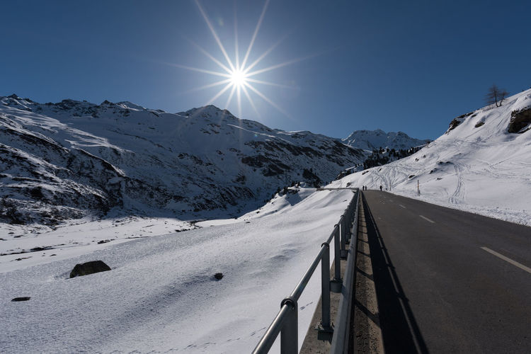 Snow Covered Road By Mountains Against Sky