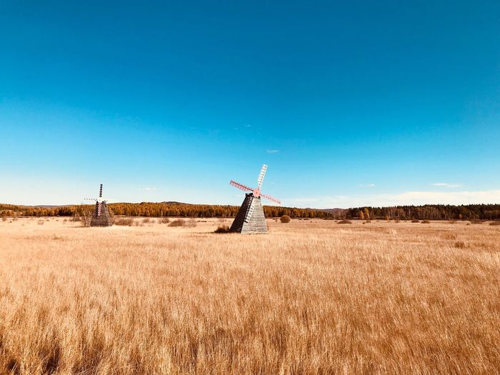 Traditional windmills on field against clear blue sky