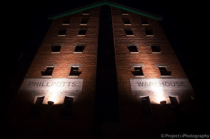 A dimly lit warehouse in Gloucester, England. Docks Gloucester England Moody Light Warehouse City Night Architecture Built Structure Illuminated Night No People Window Building Exterior Low Angle View Building History The Past Outdoors Nature Tourism Dark