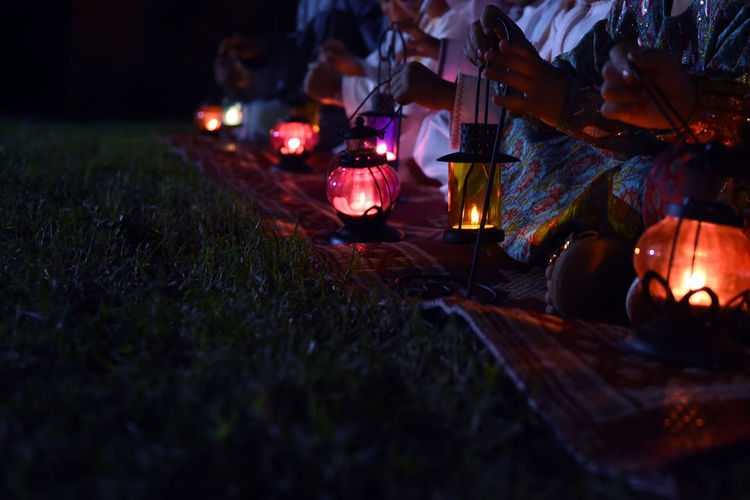 Low section of women holding lanterns while sitting outdoors at night