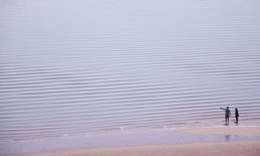 High angle view of couple standing on beach