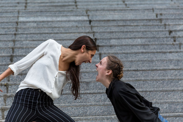 Two young women screaming at each other face to face Two People Young Adult Day Women Young Women Caucasian Indian Mixed Race Person Yelling Shouting Argument Eye To Eye Profile View Side View Staircase Anger Rage Concept Outdoors Natural Lighting Medium Shot Youth Culture ANGST