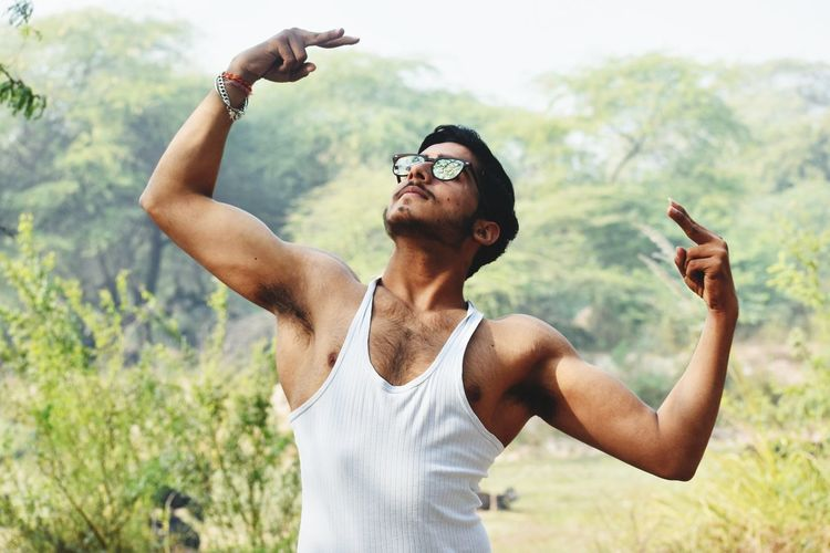 Young man gesturing while wearing sunglasses against trees