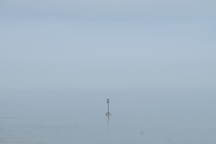 Buoy Amidst Sea In Foggy Weather