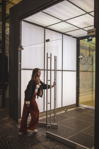 Adult Architecture Beautiful Woman Built Structure Casual Clothing Day Full Length Glass - Material Hairstyle Holding Indoors  Lifestyles One Person Real People Side View Standing Window Women Young Adult Young Women