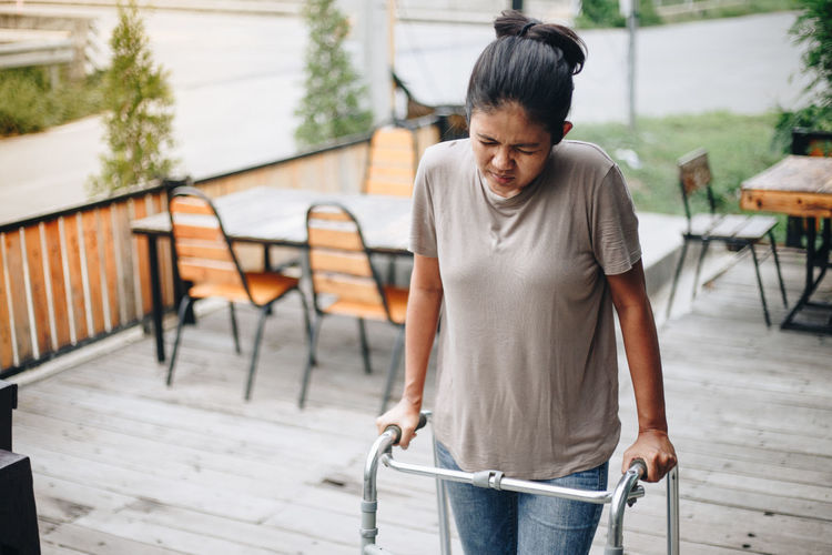 Handicapped woman standing with help of mobility walker