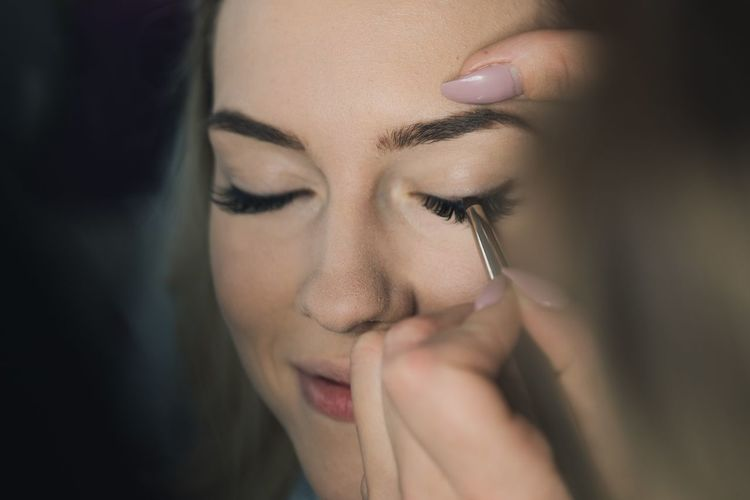 Cropped Hand Applying Make-Up To Woman