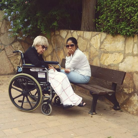 Young Women Togetherness Sitting Wheelchair Women Full Length Couple - Relationship Senior Adult Friendship Eyeglasses  Retirement Assisted Living 80-89 Years Geriatrics
