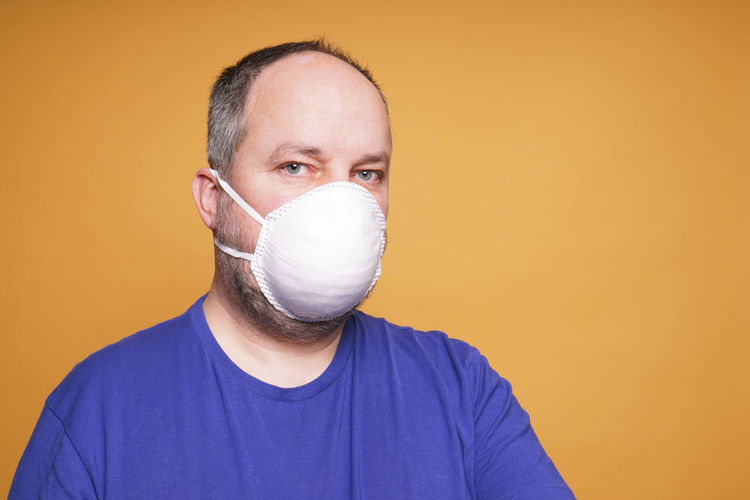 Person with face mask or dust mask or filtering facepiece - virus outbreak or air pollution concept