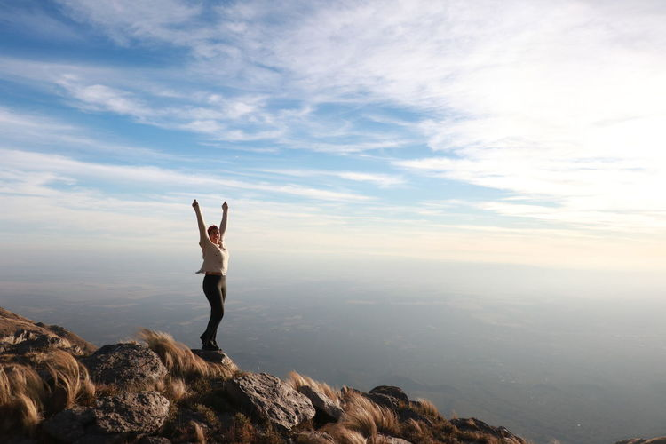 Woman with arms outstretched standing on mountain