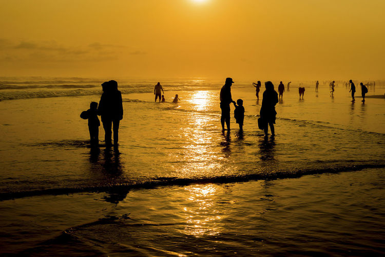 PEOPLE ENJOYING SUNSET AT PARANGTRITIS BEACH, INDONESIA Enjoying The Sun Parangtritis Yogyakarta, Indonesia Beach Land Leisure Activity Nature People On Beach Real People Sea Silhouette Sky Sunrise Sunset Travel Destinations Water