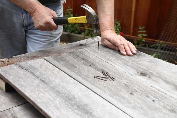 Using old wood and nails DIY Arms At Work Backyard Boards Cloudy Day Day DIY Fencing Fingers Hammer Hands Jeans Man Nails Outdoors Textures Unrecognizable Person Using Tool Wood Yard Maintenance