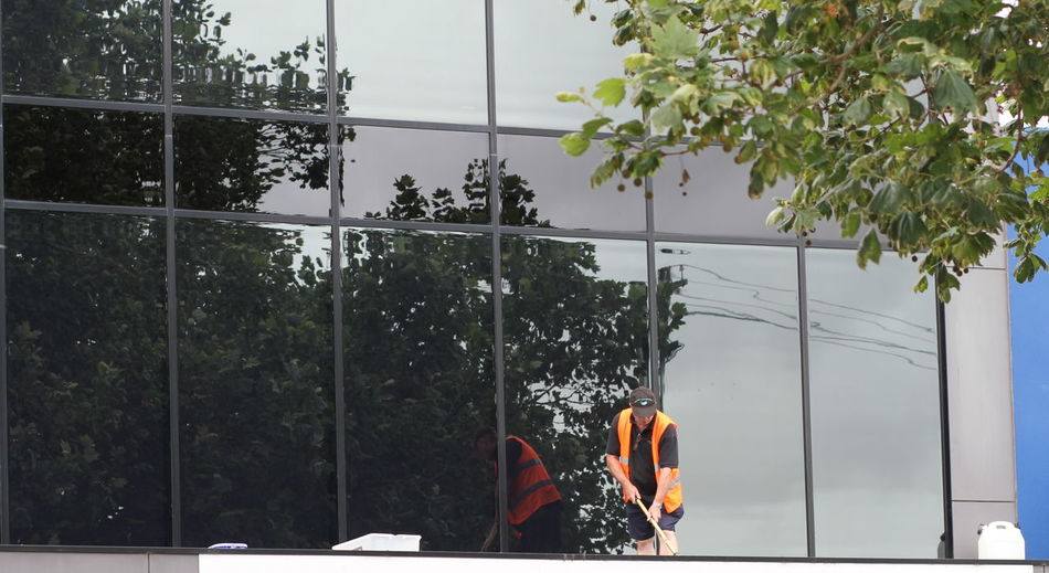 Cleaning Windows And Roofs Daytime High Vis Orange Vest Highrisebuilding Overcast Weather ❤ Trees Windows Reflection Working Hard