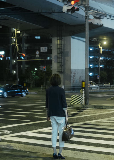 Rear view of woman standing on railroad tracks in city at night