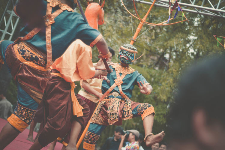 Tilt shot of men in costumes dancing during festival