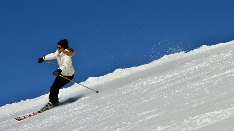 Low angle view of woman skiing on snow covered mountain against clear blue sky