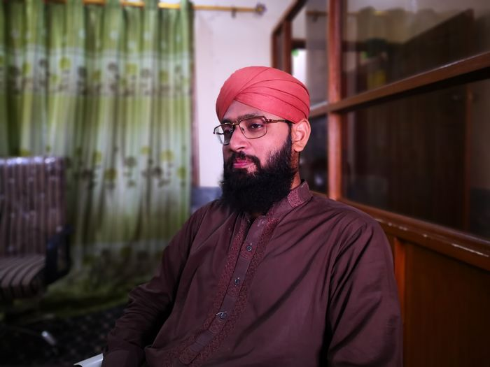 Thoughtful mature man wearing red turban while sitting on chair at home