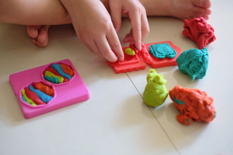 Close up of little girl's hands, child girl playing with play dough Nail Table Creativity Human Finger Lifestyles High Angle View One Person Finger Body Part Food Real People Women Child Childhood Food And Drink Multi Colored Hand Human Body Part Indoors  Human Hand Holding Leisure Activity Indoors  Art And Craft Dough
